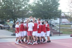 The tennis team huddles before they take on rival Floyd Central