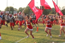 Cheerleaders running on the field with Red Devil flags.