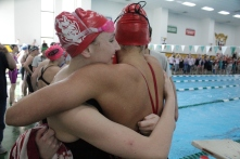 Red Devils embrace each other after winning the 200 yard medley relay.