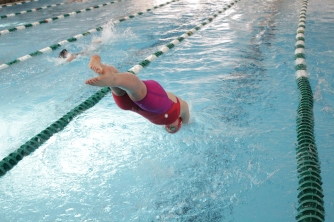 Caroline Elliott dives in the water for the 100 yard breaststroke.
