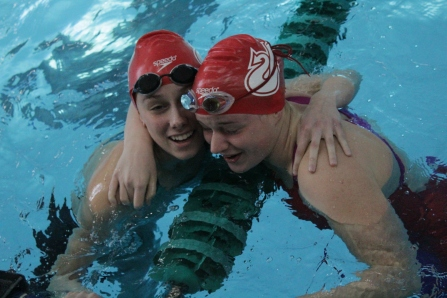 Adeline Dixon and Caroline Elliott embracing each other after placing 1st and 2nd in the 100 yard breaststroke.
