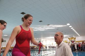 Caroline Elliott celebrating her 2nd place ribbon in the 100 yard breaststroke.