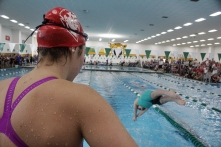 Jacqueline Richard watches Adeline Dixon diving in the water for the 400 yard freestyle relay.