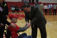 """Gary """"Cowboy"""" McCowan shaking head coach Joe Luce's hand before the game after being celebrated as the #1 Jeff fan."""