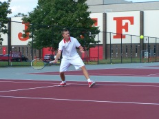 Sophomore Adam Crawford hits a forehand return to the Jeffersonville one doubles team in warm ups