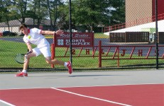 Sophomore Evan Thompson hits a forehand Friday night while practicing next to Junior Tommy Gregory