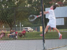 Freshman Grant Paradowski jumps to return a ball before it hits the fence at the Jeffersonville High School Invite