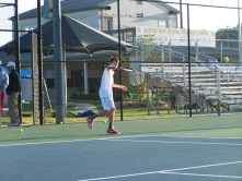 Grant Paradowski three singles hits a backhand slice shot in warm ups saturday morning
