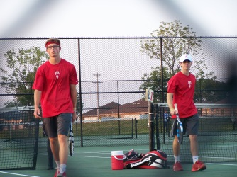 one doubles team comes back to the fence to discuss doubles strategy with Head Coach Curt Roehm